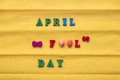 Día del día del tonto, inscripción de letras multicoloras en un fondo de papel amarillo Imagen de archivo