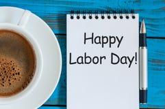 Día del Trabajo feliz - nota en la tabla con la taza de café de la mañana, 1ra del fondo de mayo Con el espacio de la copia para  Fotografía de archivo libre de regalías