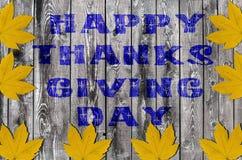 Día feliz azul de la acción de gracias escrito en fondo del tablero de madera con las hojas mucho amarillas Foto de archivo libre de regalías