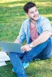 Día feliz de escuela Estudiante masculino lindo que sostiene un ordenador portátil y leído Fotos de archivo