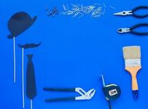 Día feliz del ` s del padre y lazo y sombrero coloridos de las herramientas en fondo azul Lugar para el texto Visión superior foto de archivo libre de regalías