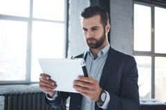 Día laborable El hombre de negocios barbudo serio en traje elegante y con el reloj calificado en su mano está pareciendo digital fotos de archivo