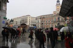 Día lluvioso en Madrid, capital de España Calle que camina con los peatones Paraguas de la lluvia foto de archivo
