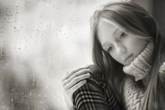 Día lluvioso: muchacha triste en la ventana blanco y negro Fotos de archivo
