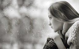 Día lluvioso: muchacha triste en la ventana blanco y negro Fotografía de archivo libre de regalías