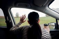 Día lluvioso o mún tiempo en un concepto de las vacaciones una mujer de la tristeza con el café caliente que se sienta en coche y foto de archivo