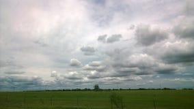 Día nublado sobre un campo verde fotos de archivo