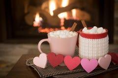 Día romántico del ` s de la tarjeta del día de San Valentín, escena caliente de la chimenea con las tazas rojas y rosadas del cac Fotos de archivo