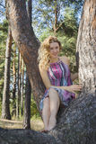 Día soleado brillante en la muchacha del bosque del otoño que se sienta en un árbol de pino Fotografía de archivo