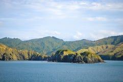 Día soleado con el fondo de la naturaleza Pequeña isla en Nueva Zelanda Colinas y montañas en verano Fotos de archivo libres de regalías