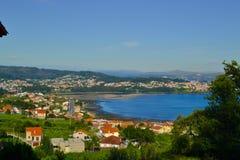 Día soleado de una pequeña ciudad delante del mar y de montañas en Galic imagen de archivo libre de regalías