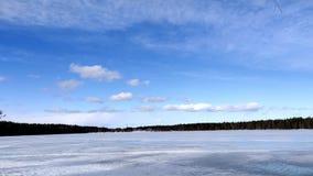 Día soleado en el lago congelado debajo del cielo azul y de la nube blanca en un día ventoso metrajes
