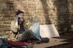 Día soleado, teléfono de carga sin hogar del viejo hombre de la batería solar imagenes de archivo