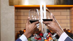 Días de fiesta, Año Nuevo y concepto de la celebración Manos masculinas que tintinean los vidrios de vino tinto en la Navidad Lug almacen de metraje de vídeo