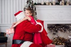 Días de fiesta, celebración, niñez y concepto de la gente - niña sonriente que abraza con Papá Noel sobre el árbol de navidad Foto de archivo