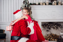 Días de fiesta, celebración, niñez y concepto de la gente - niña sonriente que abraza con Papá Noel sobre el árbol de navidad Fotografía de archivo