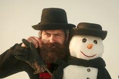 Días de fiesta del ` s del Año Nuevo Hombre de Papá Noel con el muñeco de nieve en sombrero negro Fotos de archivo libres de regalías