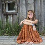 Días de fiesta en el pueblo Adolescente de la muchacha que se sienta cerca de la casa Naturaleza Imagen de archivo libre de regalías