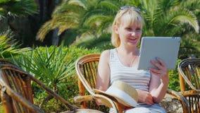 Días de fiesta en un centro turístico tropical Conectado siempre: Mujer que habla con la tableta almacen de video
