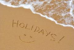Días de fiesta, escritura en la arena de la playa Foto de archivo
