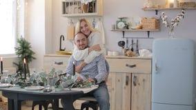 Días de fiesta, familia y concepto de la celebración - par feliz que tiene ANG de la diversión huging en casa cerca de la tabla almacen de metraje de vídeo