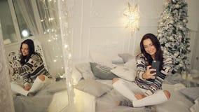 Días de fiesta, invierno y concepto de la gente - mujer joven feliz que toma el selfie sobre el árbol de navidad en casa almacen de video