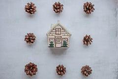 días de fiesta, invierno y concepto de la celebración - composición de la Navidad conos del pino, casa del juguete en el centro e foto de archivo libre de regalías