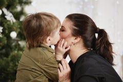 Días de fiesta, la Navidad, amor y familia feliz Niño pequeño que besa a la madre Foto de archivo