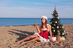 Días de fiesta de la Navidad en el mar en la playa con un cóctel Fotos de archivo libres de regalías