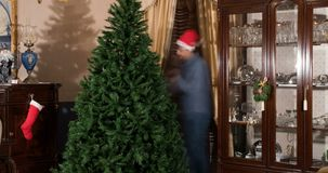 Días de fiesta de la Navidad, pares jovenes del lapso de tiempo que hacen el árbol de navidad, sombrero rojo almacen de video