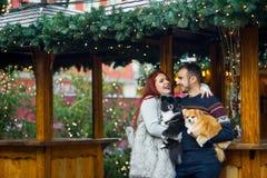 Días de fiesta de la Navidad Pares jovenes en el bazar de la Navidad con los animales domésticos Fotografía de archivo libre de regalías