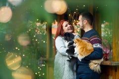 Días de fiesta de la Navidad Pares jovenes en el bazar de la Navidad con los animales domésticos Foto de archivo