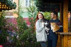 Días de fiesta de la Navidad Pares jovenes en el bazar de la Navidad con los animales domésticos Foto de archivo libre de regalías