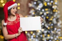 Días de fiesta, la Navidad Retrato de la mujer sonriente que lleva el sombrero de Papá Noel Foto de archivo
