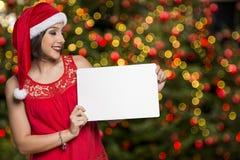Días de fiesta, la Navidad Retrato de la mujer sonriente que lleva el sombrero de Papá Noel Fotos de archivo
