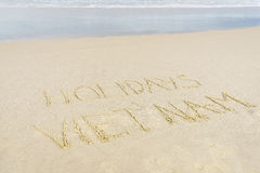 Días de fiesta Vietnam escrito en arena Foto de archivo