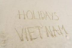 Días de fiesta Vietnam escrito en arena Fotos de archivo