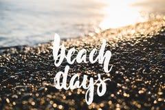 Días de la playa - frase positiva exhausta de las letras del día de fiesta de la mano en el fondo del mar o del océano de la play foto de archivo libre de regalías