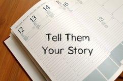 Dígales que su historia escribe en el cuaderno fotografía de archivo libre de regalías