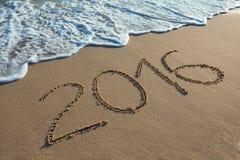 Dígito 2016 en la arena de la costa en la puesta del sol Imagen de archivo libre de regalías
