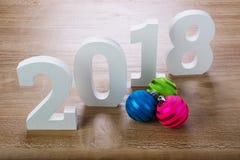 Dígitos brancos 2018 com as bolas do Natal no fundo de madeira imagem de stock