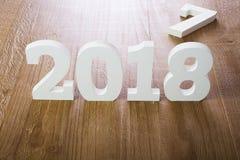 Dígitos brancos 2018 no fundo de madeira imagem de stock