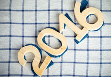 Dígitos 2016 de madeira e da sarja de Nimes em um fundo quadriculado de pano A imagem de stock royalty free