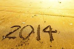Dígitos del Año Nuevo 2014 en la arena de la playa del océano Foto de archivo libre de regalías