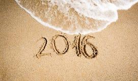 Dígitos do ano novo 2016 escritos no litoral e que estão sendo lavados fora Fotografia de Stock Royalty Free