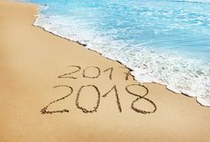 Dígitos 2017 e 2018 na areia fotos de stock