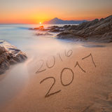Dígitos 2016 e 2017 na areia da costa no nascer do sol bonito Foto de Stock
