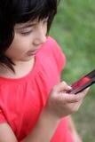 Dígitos que entran Japonés-Rusos jovenes en el teléfono Fotografía de archivo libre de regalías