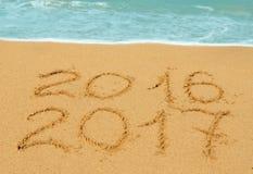 Dígitos 2016 y 2017 en la arena Imagen de archivo libre de regalías