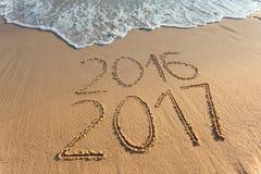 Dígitos 2017 y 2016 en la arena de la costa en la puesta del sol Fotografía de archivo